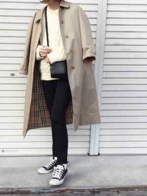 白ニットに黒スキニー、ベージュのステンカラーコートを羽織った女性
