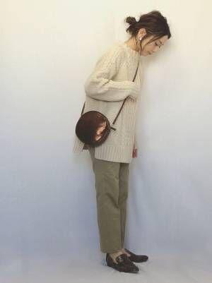 白ニットにベージュのテーパードパンツ、パイソン柄ローファーを履いた女性