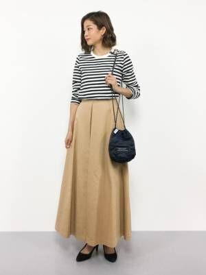 ボーダートップスにベージュのスカートを合わせて巾着バッグを持った女性