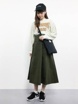 ロゴスウェットにカーキのスカートを合わせてサコッシュを持った女性