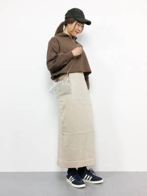 ブラウンのスウェットにスカートを合わせてクリアバッグを持った女性