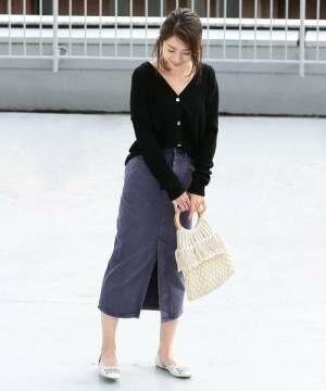 黒のトップスにパープルのデニムスカートを合わせた女性