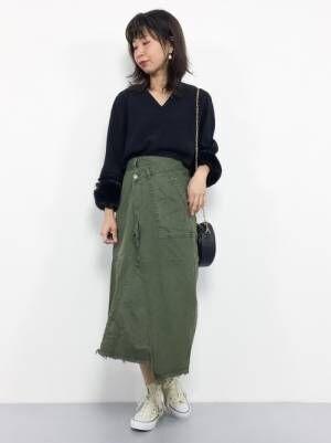 黒のトップスにグリーンのラップデザインのデニムスカートを合わせた女性