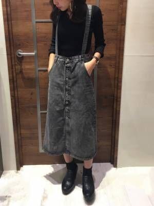黒のトップスにグレーのデニムサロペットスカートを合わせた女性