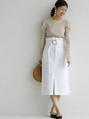 ベージュのニットに生成りのデニムスカートを合わせた女性