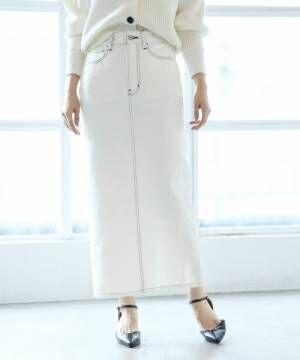白ニットに白デニムスカートを履いた女性