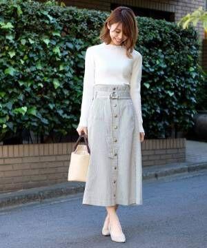 白ニットにヒッコリーデニムのスカートを合わせた女性