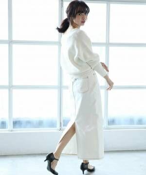 白のニットに白のデニムスカートを合わせた女性