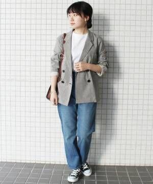 デニムパンツにテーラードジャケットを着た女性
