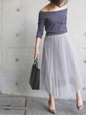 ネイビーのオフショルトップスにグレーのチュールスカートを合わせた女性