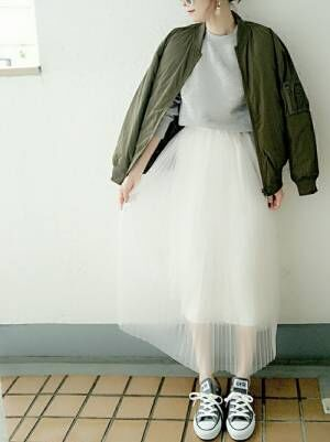 グレーのスウェットに白のチュールスカートを合わせて、カーキのMA-1を羽織った女性