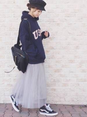ネイビーのロゴパーカーにグレーのチュールスカートを合わせた女性