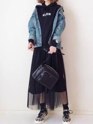 黒のパーカーにデニムジャケットを羽織って、黒のチュールスカートを合わせた女性