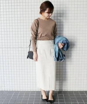 ブラウンのニットに白いスカートを合わせてデニムジャケットを持った女性