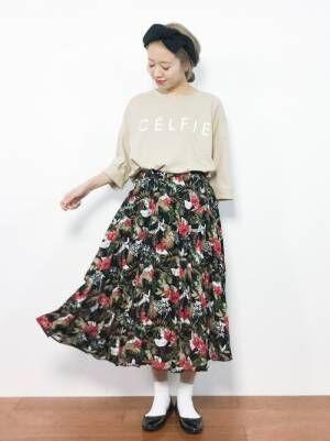 花柄のスカートにバレエシューズを合わせる女性