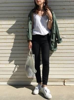 ハイライズシガレットジーンズにカーキのブルゾンを合わせる女性