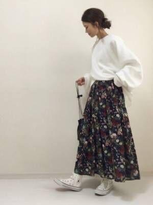 白のスウェットトップスに花柄のスカートを合わせる女性