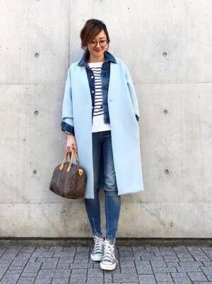 ボーダートップスにGジャンを合わせてブルーのコートを着た女性