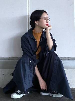 イエローのフリルネックリブニットにネイビーのシャツワンピースを着た女性