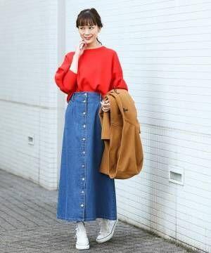 赤トップスにデニムのフロントボタンスカートを履いた女性