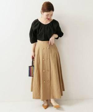 黒トップスにリネンのベージュ金ボタンスカートのコーデ
