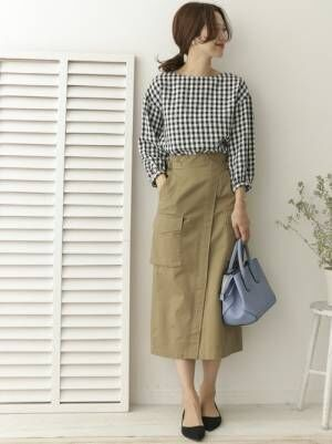ギンガムチェックのブラウスにベージュのタイトスカートを履いた女性