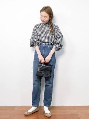 ギンガムチェックのブラウスにデニムパンツを履いた女性