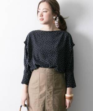 ドットブラウスにブラウンスカートを履いた女性