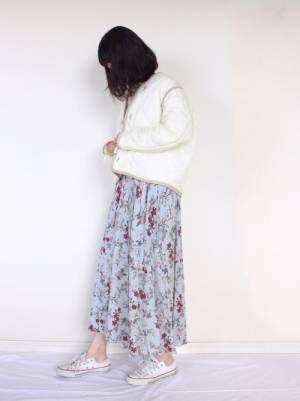 白いキルティングジャケットに花柄スカートを合わせた女性