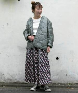 柄スカートにキルティングジャケットを着た女性