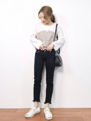 ビスチェ付きトップスに黒いパンツを合わせて白いスニーカーを履いた女性