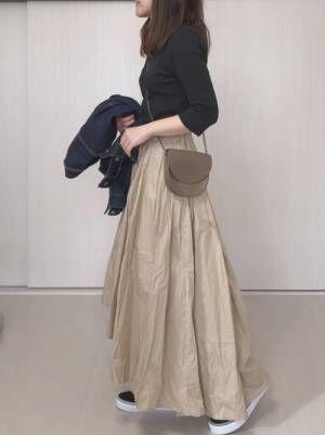 黒トップスにベージュのスカートを合わせてグレーのショルダーバッグを持った女性
