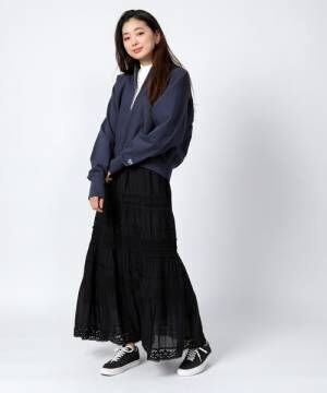 レースのスカートに黒いスニーカーを合わせた女性
