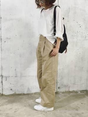 白ブラウスにチノパンを合わせて白いスニーカーを履いた女性
