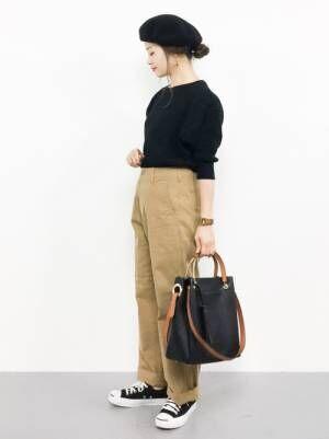 黒のトップスにチノパンを合わせて黒いバッグを持った女性