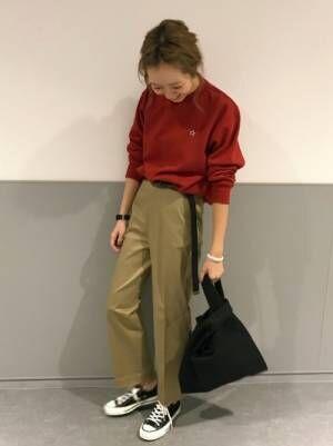赤いスウェットにチノパンを合わせて黒いスニーカーを履いた女性