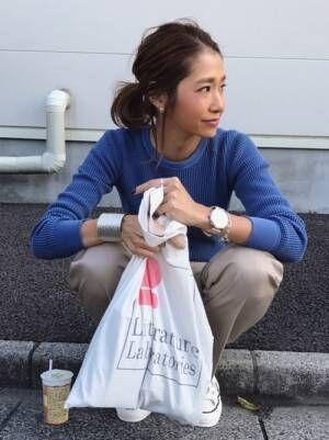 ブルーのトップスにチノパンを合わせて白いトートバッグを持った女性