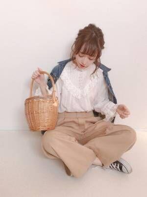 白ブラウスにチノパンを合わせてデニムジャケットを羽織った女性