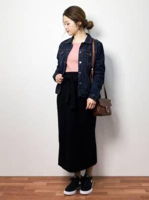 ピンクのリブニット、黒のタイトスカートにデニムジャケットを着た女性