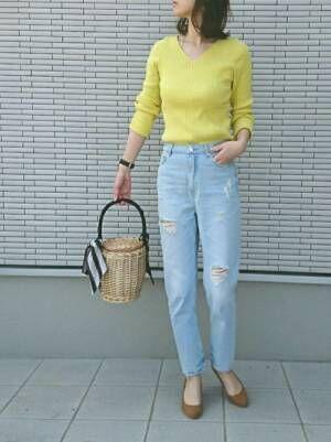黄色のリブニットにダメージデニムパンツを履いた女性