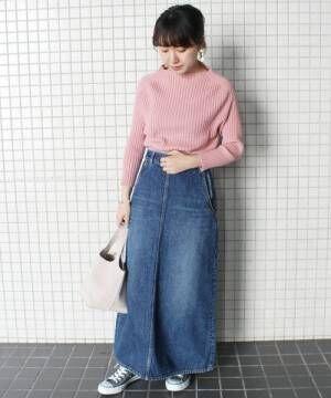 ピンクのリブニットにデニムスカートを履いた女性