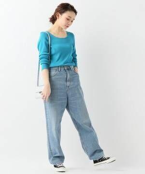 ブルーのリブニットにデニムパンツを履いた女性
