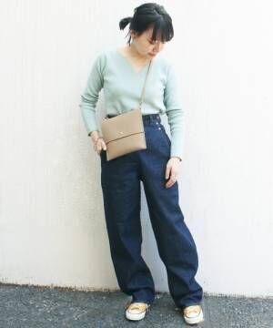ライトブルーのリブニットにデニムパンツを履いた女性