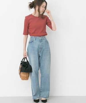 赤のリブニットにデニムパンツを履いた女性
