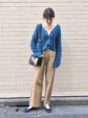 ブルーのカーディガンにベージュのチノパンを履いた女性