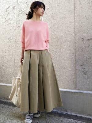 ピンクのニットにベージュのフレアスカートを履いた女性