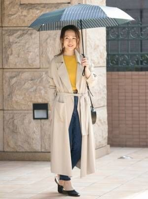 黄色のトップス、デニムパンツにベージュのトレンチコートを着た女性
