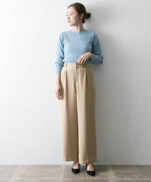 水色リブニットにベージュパンツを履いた女性
