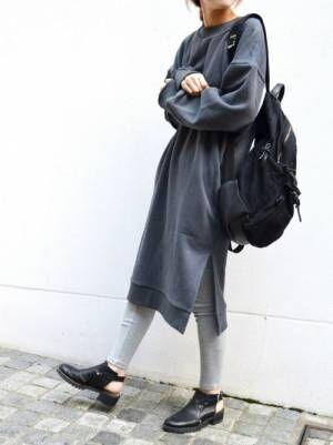 チャコールのスウェットワンピにグレーのリブレギンスを履いた女性