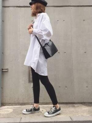 白のロングシャツに黒のリブレギンスを履いた女性